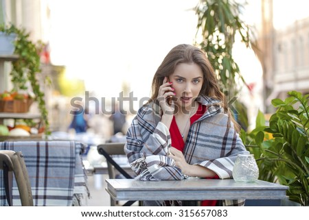 Young beautiful brunette girl sits in summer cafe in the street wrapped blanket and calling by phone