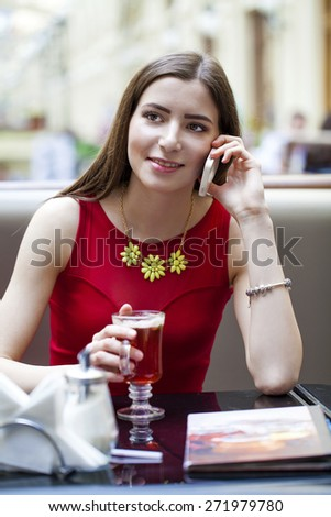 Young beautiful brunette girl sitting in a coffee shop and calling by phone - stock photo