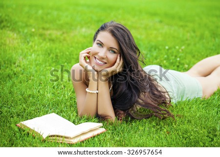 Young beautiful brunette girl with book lying on the green grass in the summer park - stock photo
