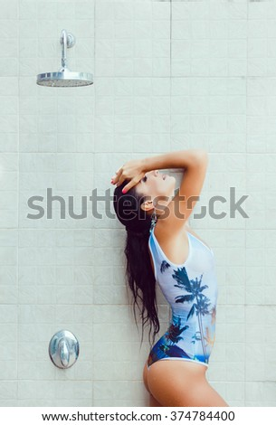 young beautiful brunette girl with long hair poses in a Villa at home in the shower, to clean, takes a shower in a swimsuit, wet tanned skin, wet hair, outdoor portrait, close up, fashion model, - stock photo