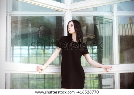 Young beautiful brunette gothic girl with perfect make-up in little black dress posing near the glass wall of the shopping center. - stock photo