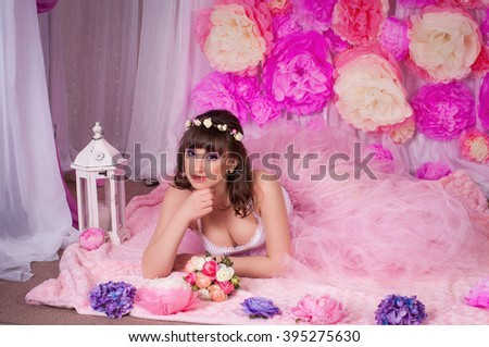 Young beautiful brunette in a studio room with floral decorations. Princess of flowers - colorful interior