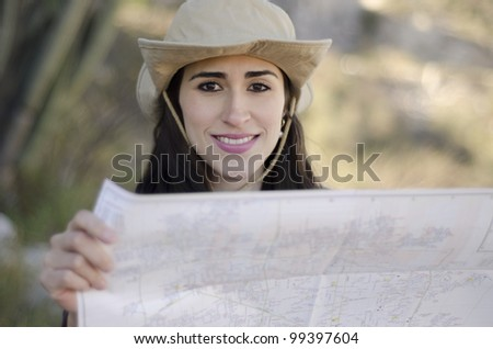 Young beautiful brunette looking at a map on a hiking trip