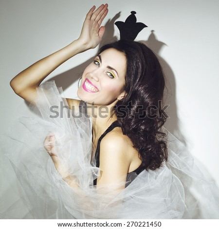 Young beautiful brunette princess in colorful clothes winking - stock photo