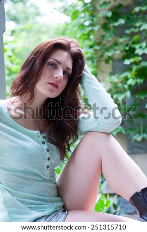 Young beautiful brunette sitting on in the park - stock photo