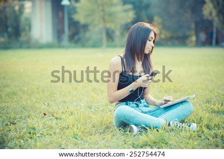 young beautiful brunette straight hair woman using tablet and smartphone sitting on grass outdoor - stock photo