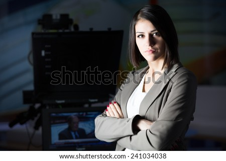 Young beautiful brunette television announcer at studio standing next to the camera.TV director at editor in studio.Recording at TV studio with television anchorwoman. TV NEWS studio with camera. - stock photo