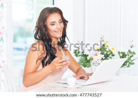 Young beautiful brunette uses laptop and phone in the kitchen