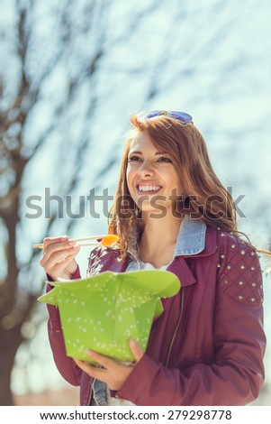 Young, beautiful brunette walking in the park on a sunny day, eating Chinese food