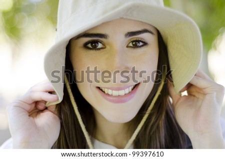 Young beautiful brunette wearing a hat on a hiking trip