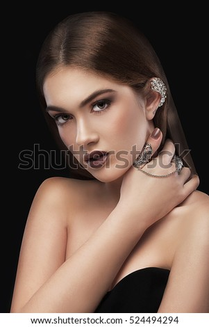 Young beautiful brunette with beautiful makeup and jewelry. Portrait of beauty. Beautiful view.