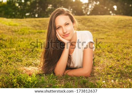 Young beautiful brunette with long hair lying on the grass and looking at the camera in sunlight