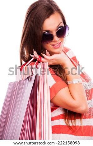 Young beautiful brunette with sunglasses holding shopping bags over shoulder, isolated on white - stock photo