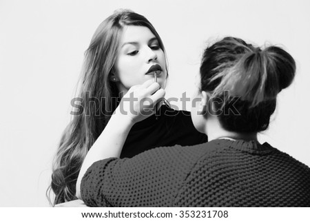 Young beautiful brunette woman applying make-up by make-up artist