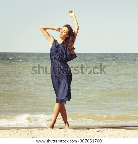 Young beautiful brunette woman at seaside in blue dress - stock photo