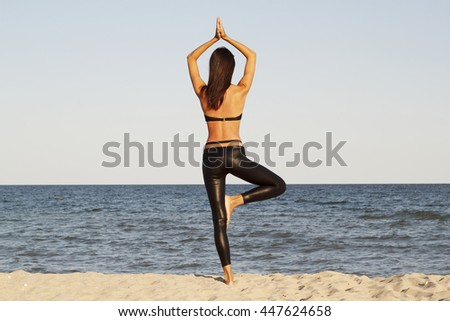 Young beautiful brunette woman doing yoga on beach in black sport costume