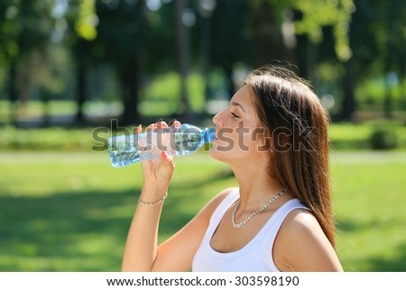 young beautiful brunette woman drinking a water from bottle in a park - stock photo