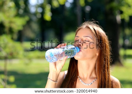 young beautiful brunette woman drinking a water from plastic bottle in a park - stock photo