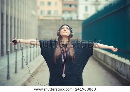 young beautiful brunette woman girl listening music headphones outdoor - stock photo