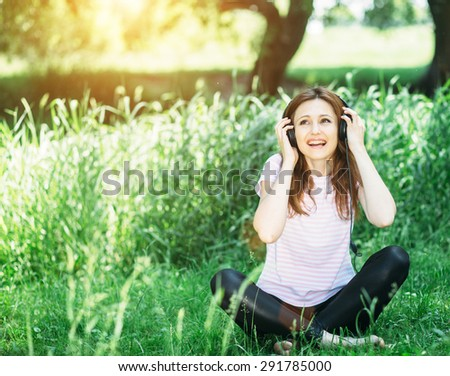 young beautiful brunette woman girl listening music headphones outdoor - stock photo