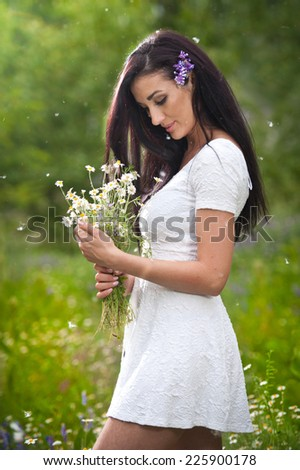Young beautiful brunette woman holding a wild flowers bouquet in a sunny day. Portrait of attractive long hair female in white dress, outdoor shot. Side view of cute girl enjoying the nature in summer - stock photo