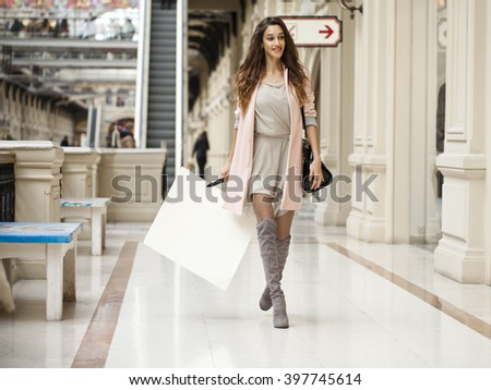 Young beautiful brunette woman in beige dress walking in the shop