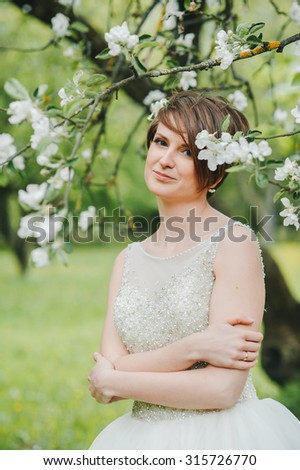 Young beautiful brunette woman in blooming garden. Bride.beautiful cute tender young blonde girl in a garden of flowering trees. Beautiful bride in wedding dress posing in a blooming apple garden. - stock photo