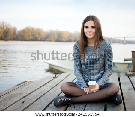 Young beautiful brunette woman in blouse and denim skirt sitting on the river pier with coffee cup