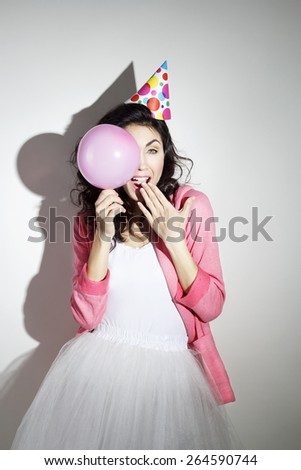 Young beautiful brunette woman in bright clothes celebrates her birthday with a pink balloon - stock photo