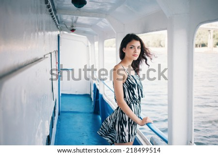 Young beautiful brunette woman in dress on the ship deck - stock photo