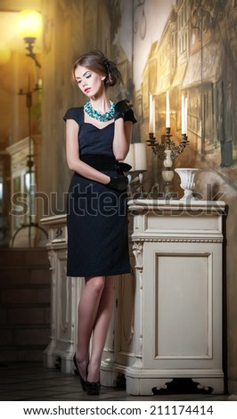 Young beautiful brunette woman in elegant black dress standing near a candlestick and wallpaper. Sensual romantic lady with creative hairstyle on high heels in luxurious vintage interior, daydreaming - stock photo