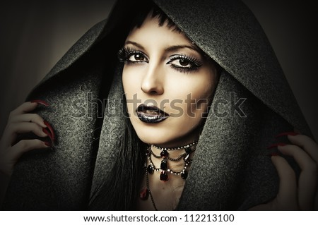 Young beautiful brunette woman in gray hood with fashion gothic make up and ancient necklace - stock photo