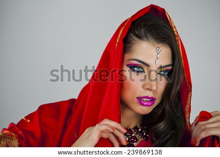 Young beautiful brunette woman in indian red dress - stock photo