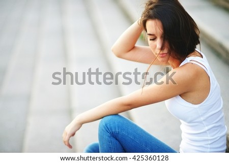Young beautiful brunette woman portrait outdoors sit on stairs. - stock photo