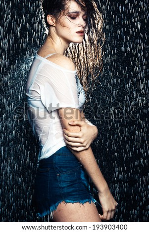 Young beautiful brunette woman posing in wet fashionable clothes - stock photo