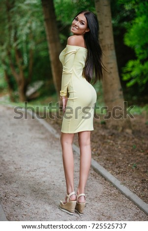 young beautiful brunette woman posing in yellow elegance dress at green summer park