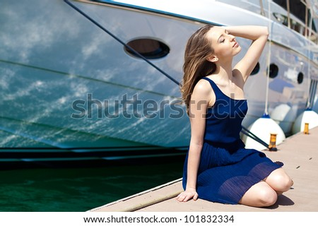 Young beautiful brunette woman relaxing on the dock near the boat on a sunny day in summer. - stock photo