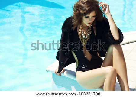 young beautiful brunette woman resting in the swimming pool