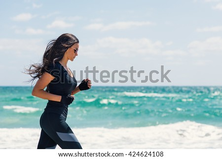 Young beautiful brunette woman running outdoors on the beach. Miami, Florida. - stock photo
