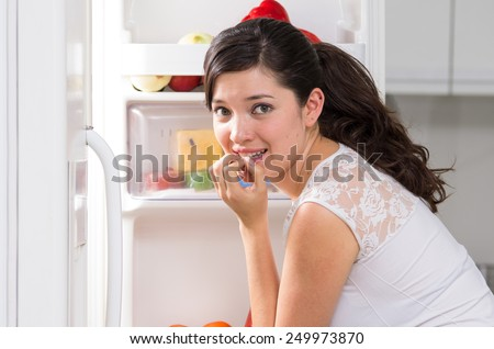 young beautiful brunette woman searching for food in the fridge looking nervous - stock photo