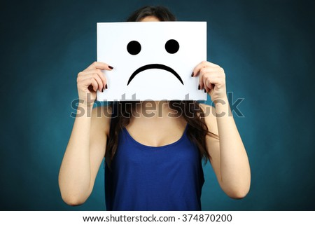 Young beautiful brunette woman showing a sad emoticon on blue background