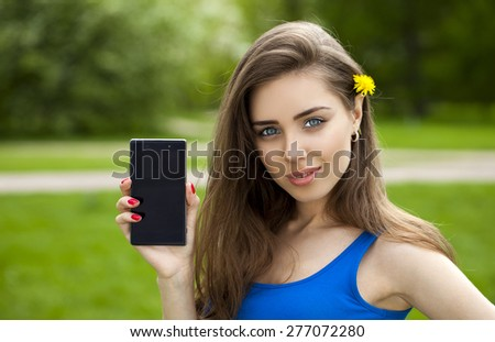 Young beautiful brunette woman shows a new smart phone, outdoor background - stock photo