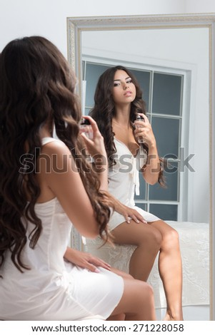Young beautiful brunette woman sitting against mirror and applying perfume - stock photo