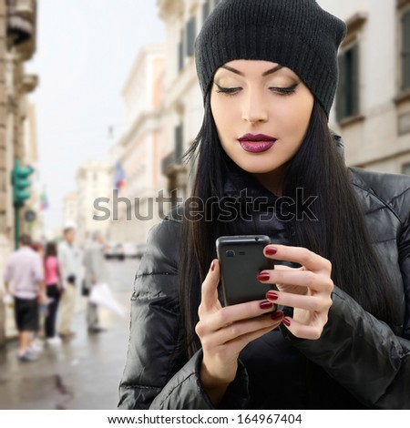 Young beautiful brunette woman touching and browsing her smart phone over city background - stock photo