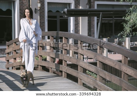 Young beautiful brunette woman walking with dog on wooden bridge - stock photo