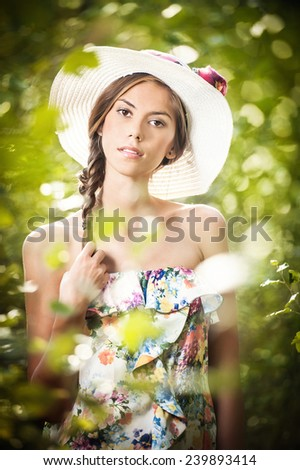 Young beautiful brunette woman wearing a large hat in a sunny day. Portrait of attractive long hair female with multicolored blouse, outdoor shot in a garden. Pretty girl enjoying the nature in summer - stock photo
