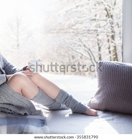 Young beautiful brunette woman with cup of coffee wearing knitted cardigan sitting home relaxing by the window. Snowy winter home chill out concept - stock photo