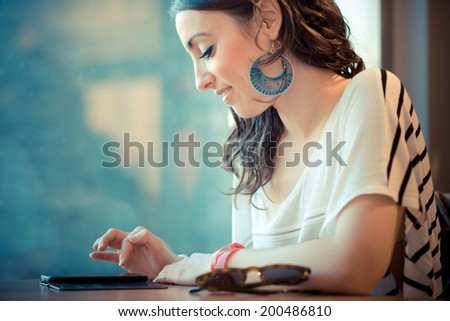 young beautiful brunette woman with smart phone at the bar - stock photo