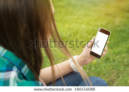 Young beautiful brunette woman with smart phone in park. Closeup of teenage girl's hand holding a smart phone white blank isolated screen. Technology and modern lifestyle concept.