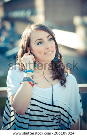 young beautiful brunette woman with smart phone listening music  in the city